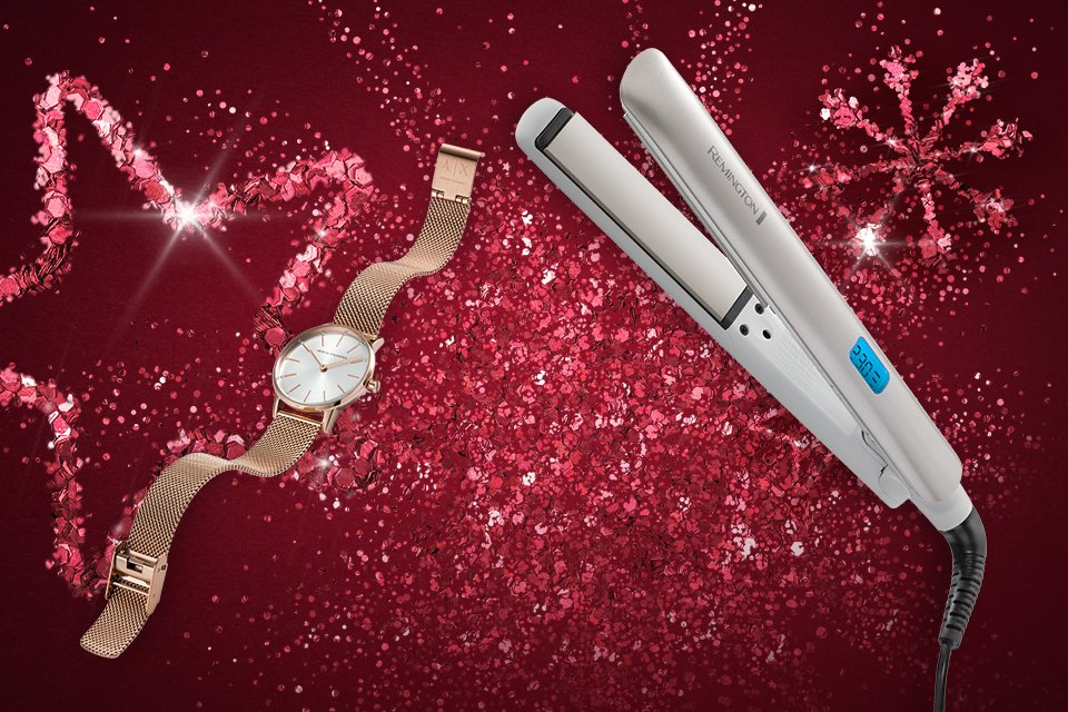 Some hair straighteners and a watch in front of a pink glittery background.
