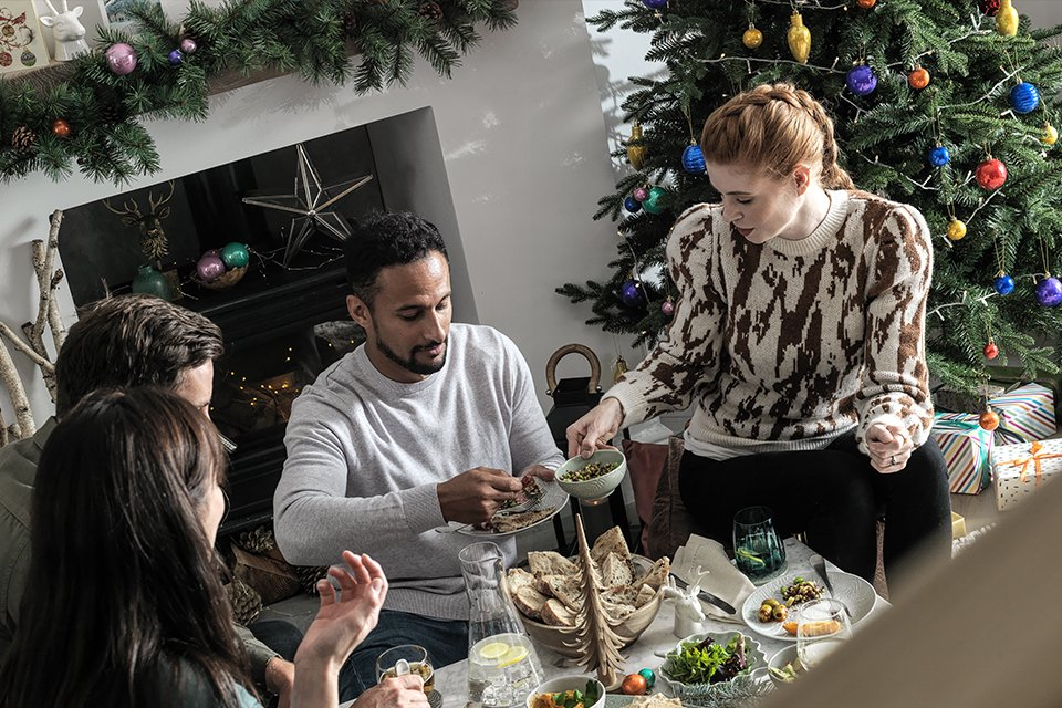 Four people sat around a table eating Christmas dinner.