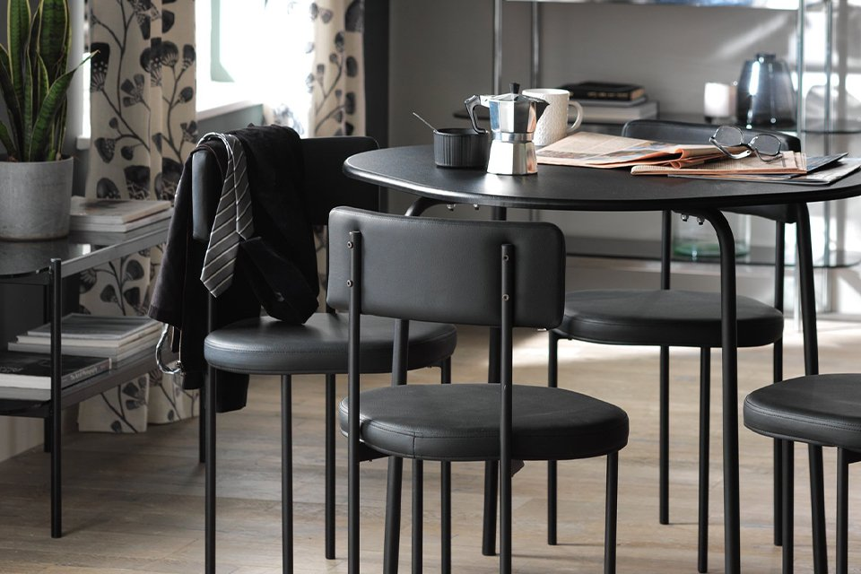 A black dining table with a set of 4 matching chairs.