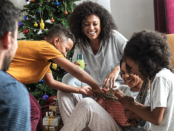 A family opening gifts together on Christmas day.