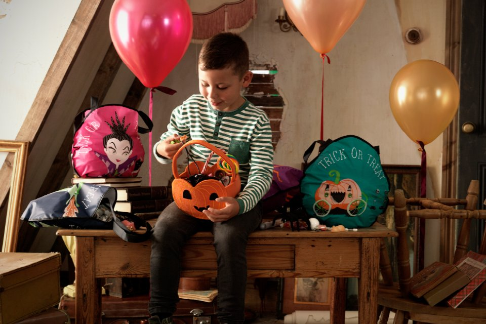 A child sitting on a table picking out sweets from his pumpkin basket. Halloween bags and balloons surround him.