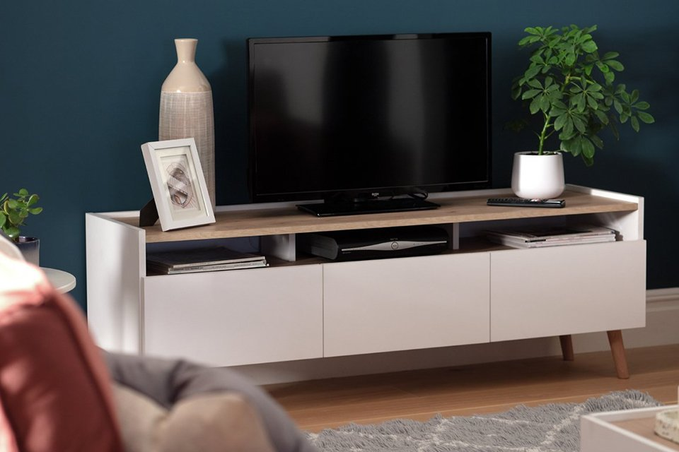 A television sat atop a unit also being used to show picture frames and potted plants in a living room.