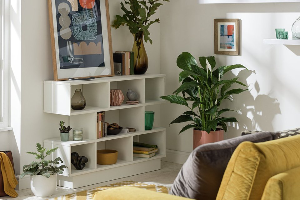 A bookcase filled with home furnishings and books in a living room.