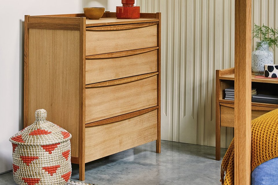 A set of wooden drawers with a lamp sitting on top of them.
