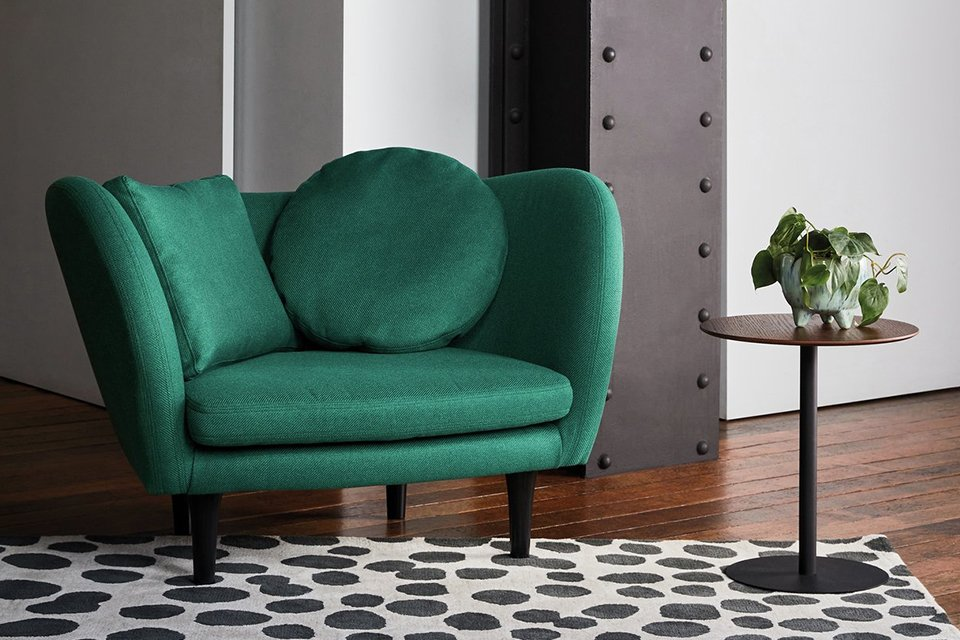 A green Habitat armchair in the centre of a room sat on a plush rug.
