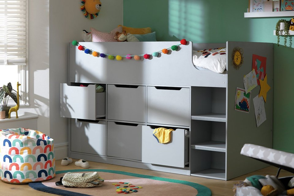 A grey Habitat raised bed with storage drawers in a childs bedroom.