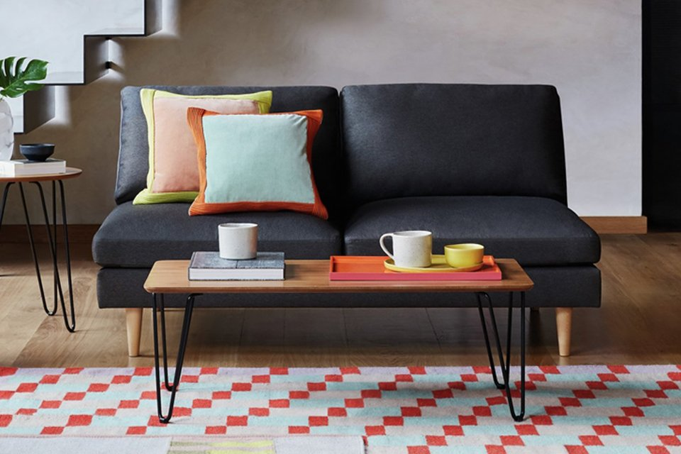 A charcoal Habitat sofa sat in the centre of a living room behind a coffee table laid with books and mugs.