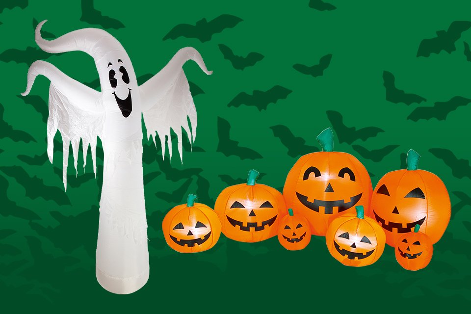 A collection of smiling pumpkins of different sizes and a smiling inflatable ghost.