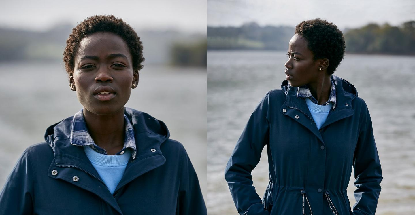 Woman wearing a navy blue rain coat over a pale blue crew neck jumper & check shirt.
