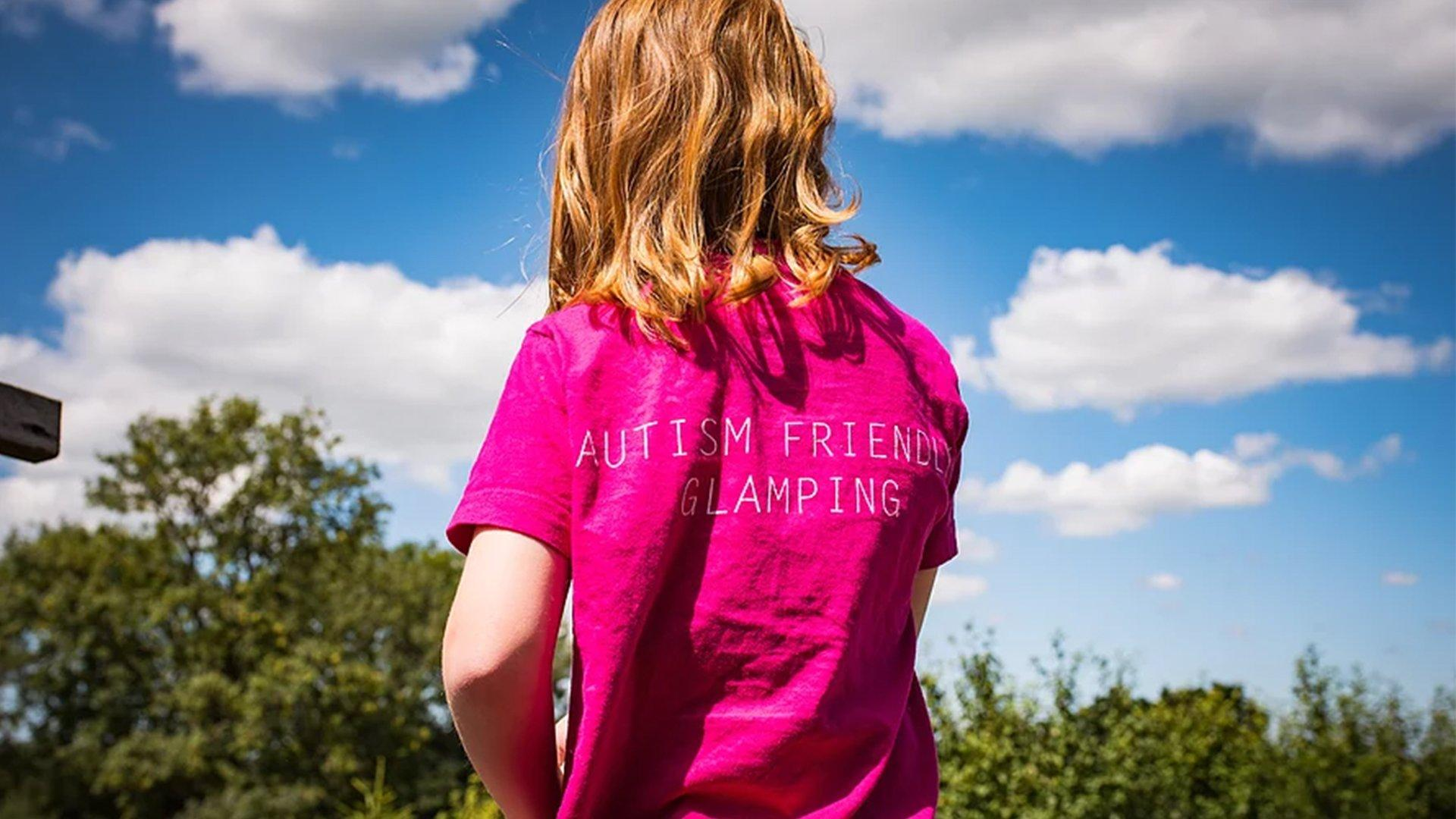 Image of a child wearing a t-shirt that promotes autism friendly camping at Leafy Fields Campsite