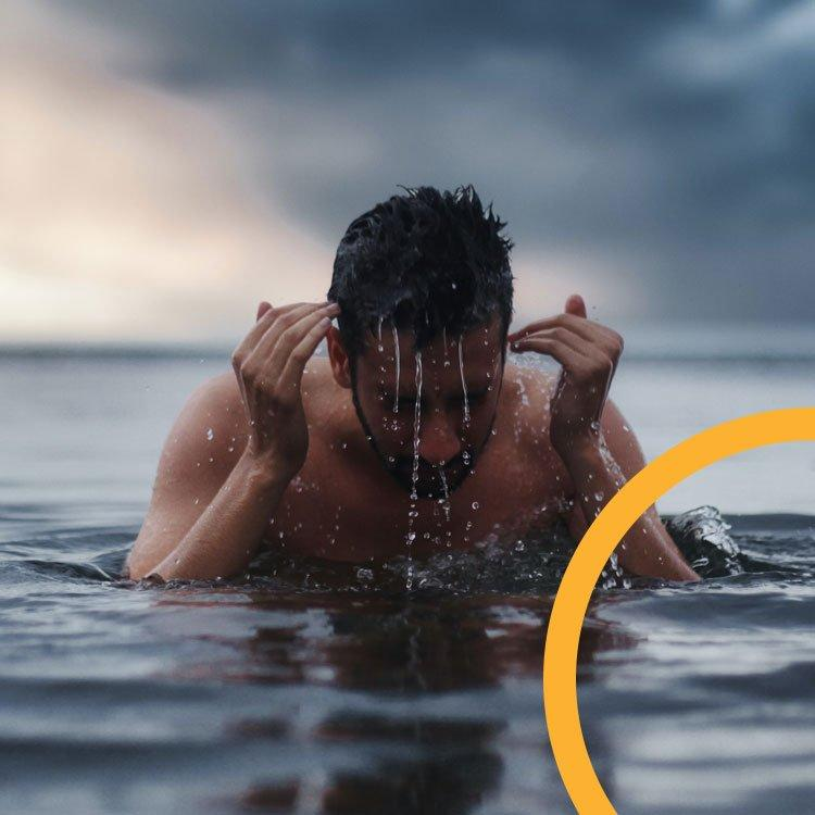 An image of a man swimming outdoors who has just broken the surface of the water.