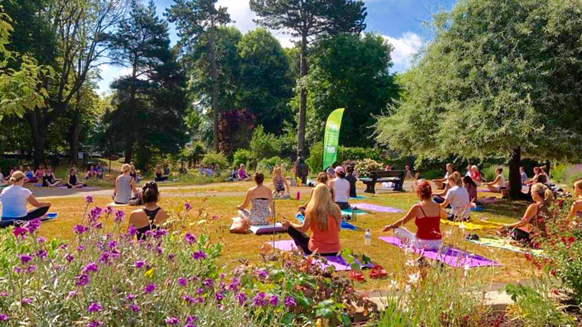 a group of people practicing yoga in a park in the UK