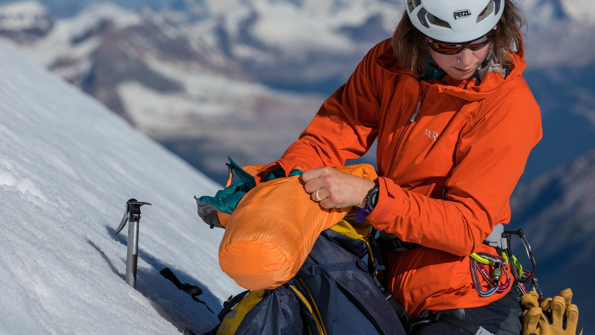 outdoor adventurer packing a Rab Microlight jacket into a compact stuff sack